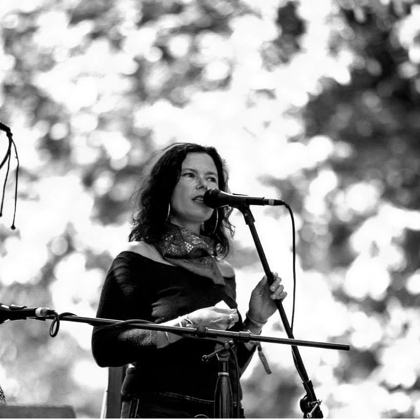 black and white photo of rain crowe, white skinned woman with shoulder length hair speaking into a microphone