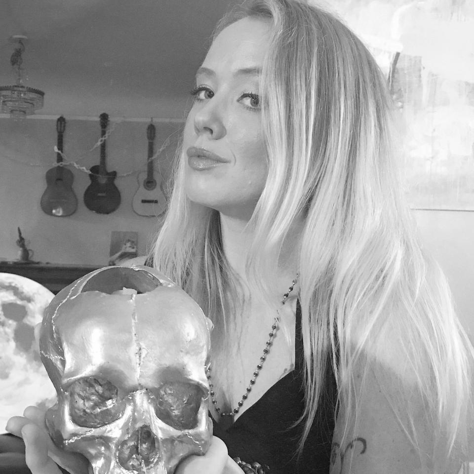 black and white photo of rachael rice, white-skinned woman with blond hair holding a skull