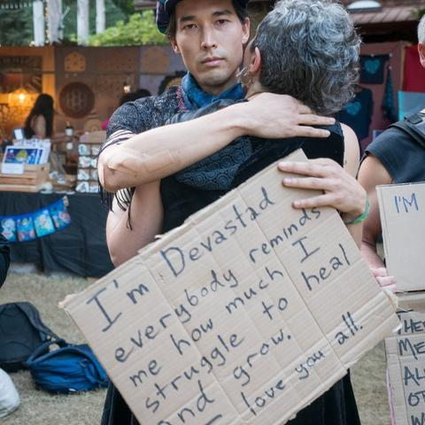 Two people hugging holding Vulnerability signs.
