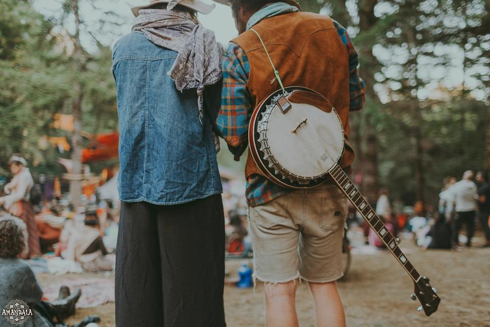 two people stand side by side, one with a banjo slung over their back