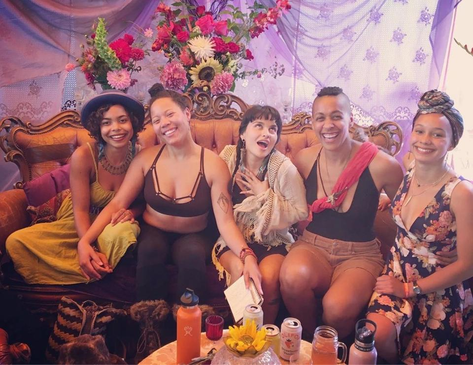 Some of the BIPOC Sanctuary organizers on a yellow velvet couch smiling